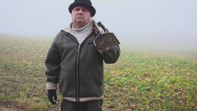 Starszy rolnik trzyma błotnistego pitchfork na polu i motykę z kapeluszem Ręczna praca mgła zbiory wideo