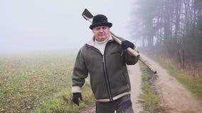 Starszy rolnik trzyma błotnistego pitchfork na polu i motykę z kapeluszem Ręczna praca mgła zbiory