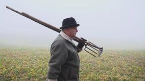 Starszy rolnik trzyma błotnistego pitchfork na wiosny polu i motykę z kapeluszem Ręczna praca mgła zbiory