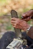 Starszy rolnik usługuje jego piłę łańcuchową po use Obrazy Stock