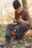 Starszy rolnik usługuje jego piłę łańcuchową po use Zdjęcie Royalty Free
