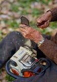 Starszy rolnik usługuje jego piłę łańcuchową po use Fotografia Stock