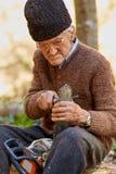 Starszy rolnik usługuje jego piłę łańcuchową po use Zdjęcie Stock