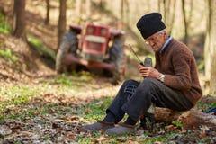 Starszy rolnik usługuje jego piłę łańcuchową po use Obraz Stock