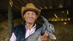 Starszy rolnik w słomianym kapeluszu trzyma wielkiego szarego królika Portret mężczyzna w tle siano zdjęcie wideo