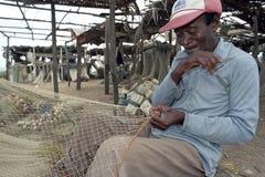 Starszy rybak siedzi naprawiać fishnet Zdjęcia Stock