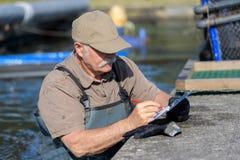 Starszy rybiego gospodarstwa rolnego pracownik bierze notatki na schowku Fotografia Stock