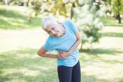 Starszy sprawności fizycznej kobiety nacierania mięśnie jej prawa strona zdjęcie stock
