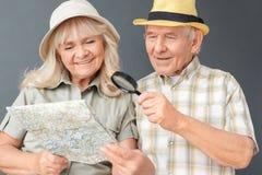 Starszy turyści patrzeje mapę szczęśliwą w górę w plażowych kapeluszy pracownianej pozycji odizolowywającej na szarym mienia magn zdjęcie royalty free