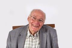 Starszy uśmiechnięty mężczyzna obsiadanie na krześle obraz stock
