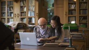 Starszy wykładowca i młoda kobieta dyskutuje temat przy stołem w bibliotece zbiory wideo