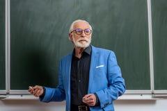 starszy wykładowca trzyma kawałek kreda zdjęcie royalty free