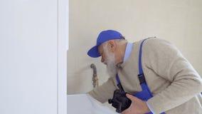 Starszy z włosami mężczyzna jest ubranym coveralls naprawy kotłowe zbiory