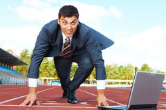 At start. Image of businessman getting ready for race with laptop near by Stock Photos