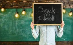 Start av skolårbegreppet Läraren rymmer den svart tavlan främst av framsida Mannen välkomnar studenter, svart tavla på bakgrund royaltyfria bilder