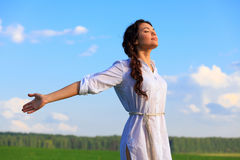 Start breathing clean air. Young happy woman breathing clean and fresh air in green field Royalty Free Stock Images