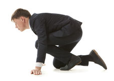 Start businessman. Isolated young businessman kneeling as if about to start a race Stock Images