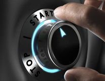 Start Button. Man hand turning a start and stop button over grey background, Concept of action Royalty Free Stock Image