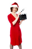 Start...Camera! Action!. Smiling female santa holding a clapperboard Stock Image