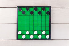 Start checker game on green board view from above on table. Start checker game on green board view from above on wood table royalty free stock image