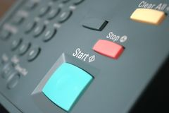 Start copying / Printing. Green Start Button on a photo copier/fax/printer.  Shallow focus, on work start Stock Photography