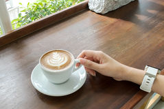 Start The Day with Good Cup of Coffee Concept. Perspective View Business Asian Woman Hand Holding Cup of Cappuccino Coffee. With Tree Design Foam on Wooden Stock Photos