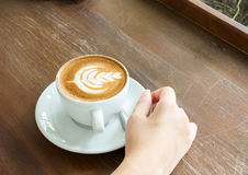 Start The Day with Good Cup of Coffee Concept. Perspective View Business Asian Woman Hand Holding Cup of Cappuccino Coffee. With Tree Design Foam on Wooden Royalty Free Stock Photography