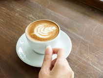 Start The Day with Good Cup of Coffee Concept. Perspective View Business Asian Woman Hand Holding Cup of Cappuccino Coffee. With Tree Design Foam on Wooden Stock Photo