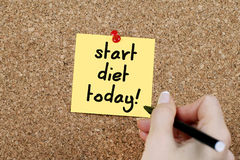 Start Diet Today. Woman hand writing'start diet today' on adhesive note pinned on cork noticeboard stock photo