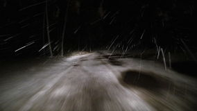 Start driving through the winter forest on snowy road at night stock footage