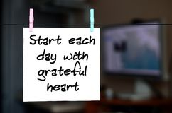 Start each day with grateful heart. Note is written on a white s. Ticker that hangs with a clothespin on a rope on a background of office interior stock images