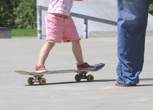 Start 'em young. Dad teaches his young daughter how to handle the skateboard at the local skatepark Stock Images
