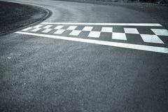 Start finish line on windy asphalt road. Sunny finish and start line pattern on the winding asphalt race road royalty free stock photos