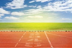 Start and Finish point of race track ,Running track number in fr. Ont of tracks in stadium with beautiful green grass with blue sky scenery background royalty free stock photography