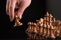Start of the game with gold chess. The hand holds the shape. Black background with reflections Royalty Free Stock Images