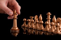 Start of the game with gold chess. The hand holds the shape. Black background with reflections Royalty Free Stock Photography