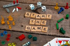 `Start the Game` made from Scrabble game letters. Risk, Battleship pieces, Monopoly, Settler of Catan and other game pieces royalty free stock photo