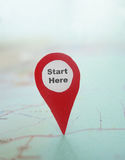 Start Here locator. Red locator symbol with Start Here text on a map stock photography