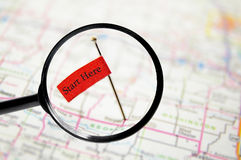 Start here. Pin with stuck into a map with magnifying glass and Start Here text Stock Photo