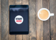 Start Here. Tablet and cup of coffee are on the table. Start here button is on the screen Stock Photography
