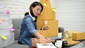 Start het kleine bedrijfsondernemersmkb of freelance Aziatische vrouw die online markt verpakking met doos thuis concept werken