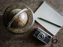 Start The Journey. The Classic World Globe with Vintage Camera, Light Brown Notebook, Green Pencil on Old Wooden Backgroud for Traveller Journey Concept royalty free stock image