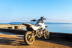 Start The Journey Concept, Old Small White Motorcycle with Blue Sea and Sky in Background Stock Image