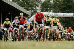 Start large group of athletes cyclists mountain bikers stock images