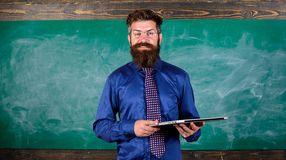 Start lesson. Teacher bearded man with modern laptop chalkboard background. Modern technology education. Hipster teacher. Wear eyeglasses and necktie holds royalty free stock photos