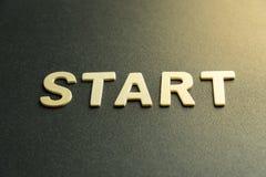 Start letter. Wooden letter of word  start on black background Stock Image