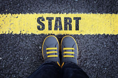 Start line. Child in sneakers standing next to a yellow starting line royalty free stock photo