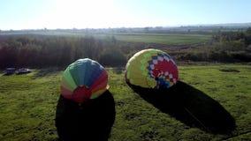 Start lotniczy balon przy zmierzchem, lotniczy balony zaczyna komarnicy od trawy pola przy lato zmierzchem, lotniczy balony na po zbiory