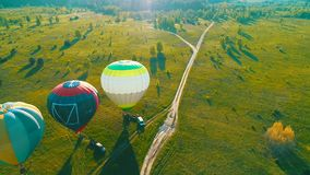 Start lotniczy balon przy zmierzchem, lotniczy balony zaczyna komarnicy od trawy pola przy lato zmierzchem, lotniczy balony na po zdjęcie wideo