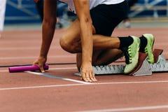 Start man runner with baton. In hand relay race running Stock Photos